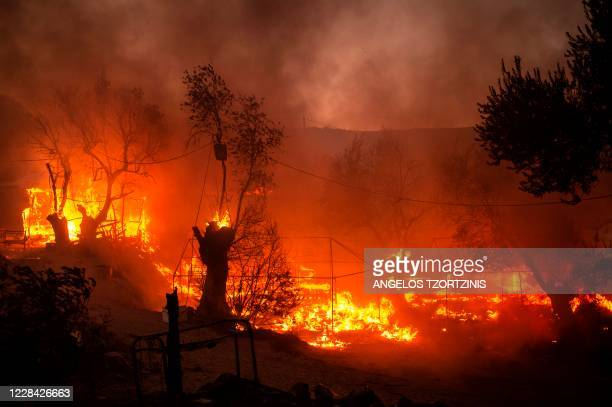 Housing structures and vegetation burn after major fire broke out in the Moria migrants camp on the Greek Aegean island of Lesbos, on September 9,...