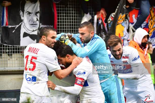 Houssem Aouar of Lyon is mobbed by teammates after scoring a very late winning goal during the Ligue 1 match between Amiens SC and Olympique Lyonnais...