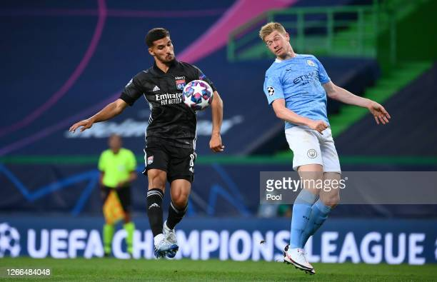 Houssem Aouar of Olympique Lyon is challenged by Kevin De Bruyne of Manchester City during the UEFA Champions League Quarter Final match between...