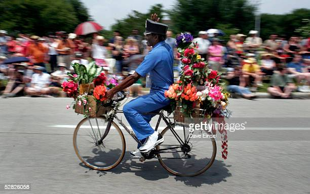 Houston artist Flower Man rides his bicycle during the Everyone's Art Car Parade May 14 2005 in Houston Texas The parade includes around 280 cars and...