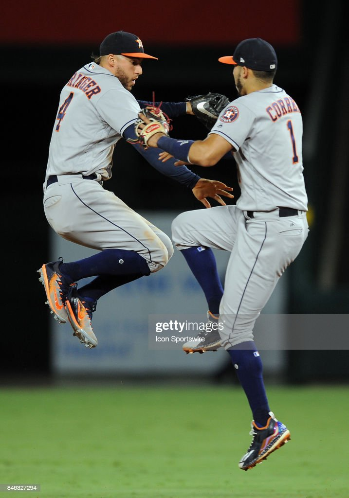 Houston Astros center fielder George Springer (4) and shortstop Carlos Correa (1) leap in the air after the Astros defeated the Los Angeles Angels of Anaheim 1 to 0 in a game played on September 12, 2017 at Angel Stadium of Anaheim in Anaheim, CA.