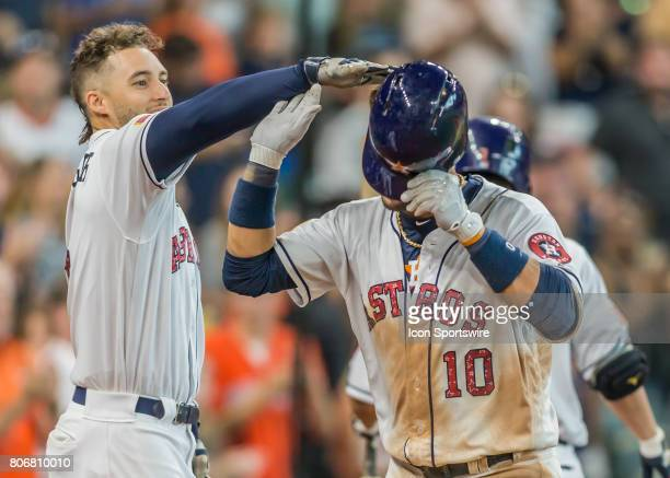 Houston Astros center fielder George Springer gives a friendly tap on the head to Houston Astros first baseman Yuli Gurriel after hitting a home run...