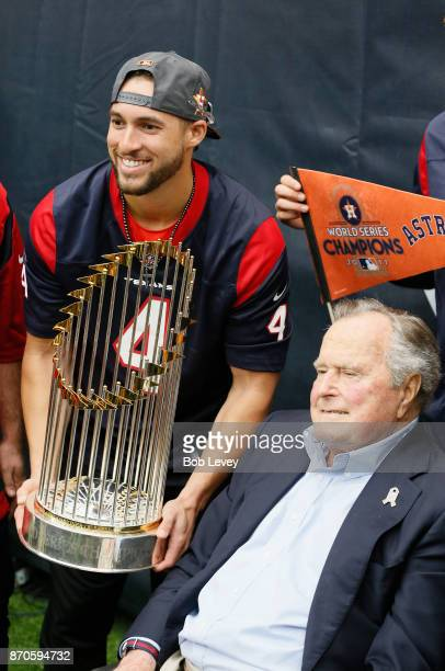 Houston Astros George Springer and former President George HW Bush pose for a picture with the Commissioner's Trophy in the second quarter at NRG...