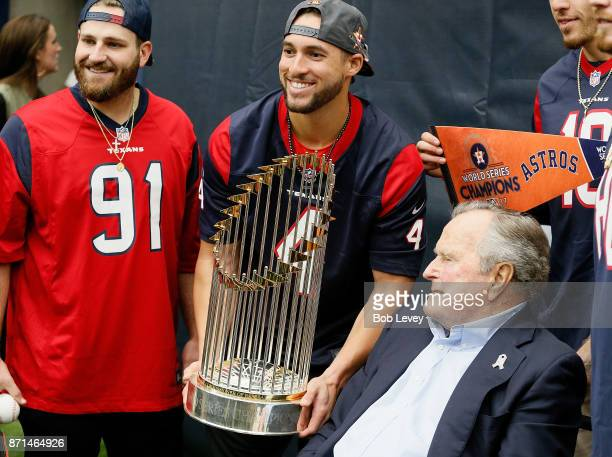 Houston Astros George Springer holds the 2017 World Series Championship trophy as he takes a photograph with former President George HW Bush at NRG...