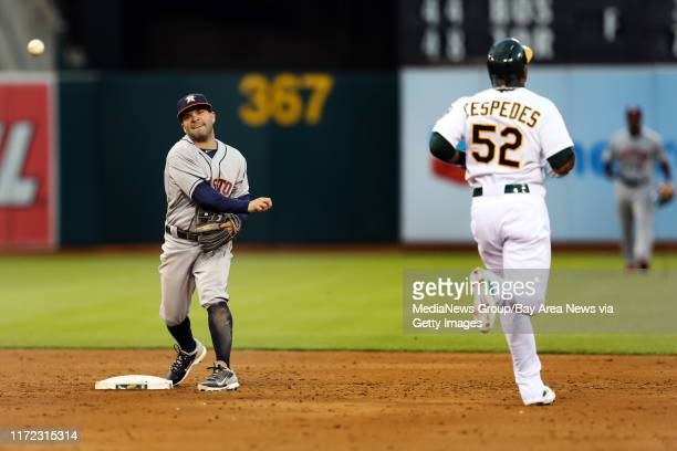 Houston Astros' Jose Altuve attempts to throw out Oakland Athletics' Josh Donaldson at first as Yoenis Cespedes is out at second in the third inning...