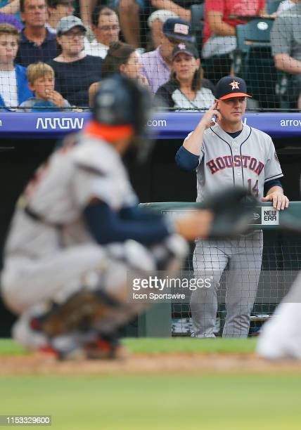 Houston Astros manager AJ Hinch gives a pitch sign to catcher Robinson Chirinos during a game between the Colorado Rockies and the visiting Houston...