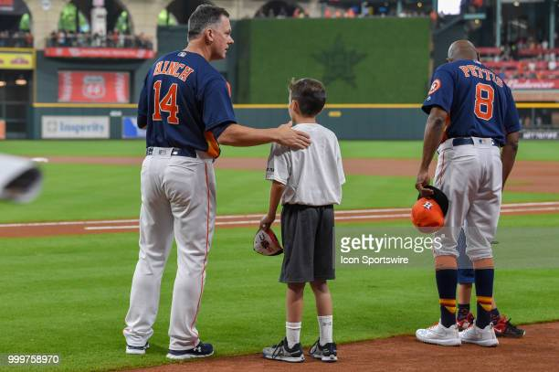 Houston Astros manager AJ Hinch lines up for the National Anthem with a young ball player before the baseball game between the Detroit Tigers and the...