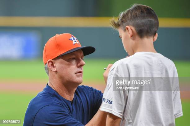 Houston Astros manager AJ Hinch signs a child's shirt before the baseball game between the Detroit Tigers and the Houston Astros on July 15 2018 at...