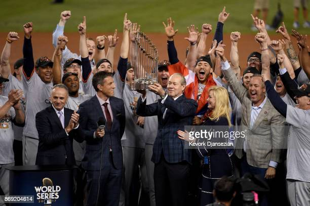 Houston Astros owner and chairman Jim Crane hoists the Commissioner's Trophy after the Astros defeated the Los Angeles Dodgers 51 in game seven to...