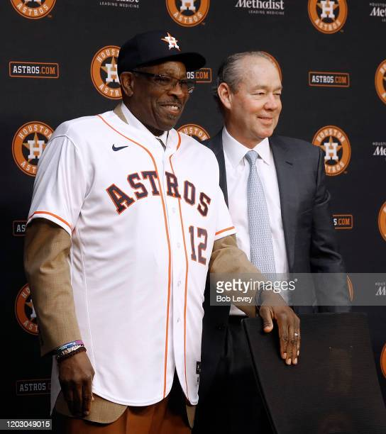 Houston Astros owner Jim Crane helps Dusty Baker try on his jersey as he is officially introduced as their new manager at Minute Maid Park on January...