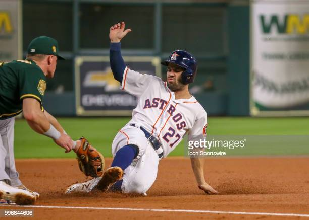 Houston Astros second baseman Jose Altuve slides into third base during the baseball game between the Oakland Athletics and Houston Astros on July 9...