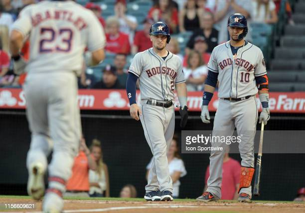 Houston Astros shortstop Alex Bregman and third baseman Yuli Gurriel wait at the plate for designated hitter Michael Brantley after Brantley hit a...