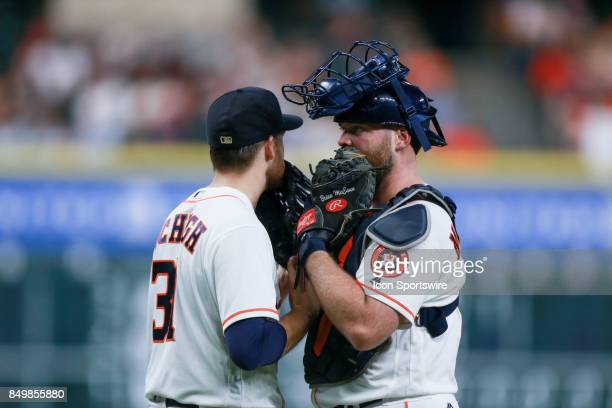 Houston Astros starting pitcher Collin McHugh and Houston Astros catcher Brian McCann cover their mouth while talking to each other on the field in...