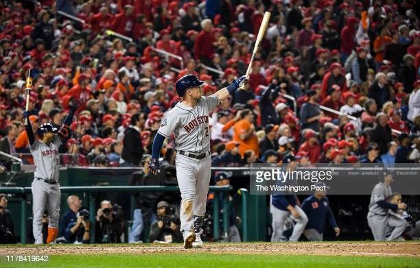 Houston Astros third baseman Alex Bregman holds his bat high as his seventh-inning grand slam sails into the stands during Game 4 of the World Series...
