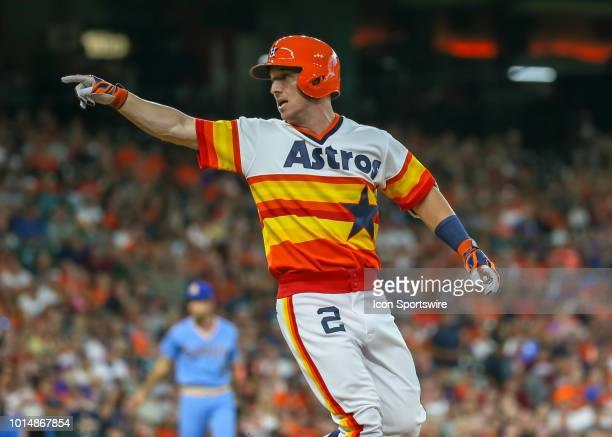 Houston Astros third baseman Alex Bregman points to the dugout wearing a 1970s uniform during the baseball game between the Seattle Mariners and...