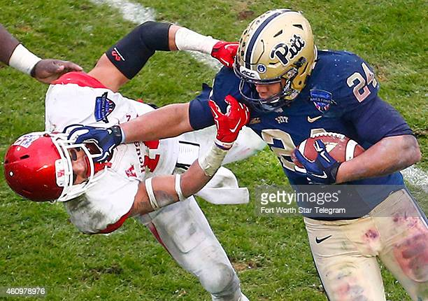 Houston defensive back Adrian McDonald is stiffarmed by Pittsburgh running back James Conner in the fourth quarter in the Armed Forces Bowl at Amon G...
