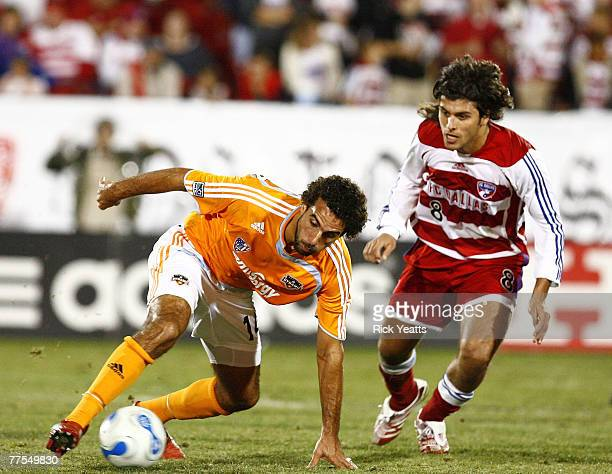 Houston Dynamo midfielder Dwayne De Rosario moves the ball away from FC Dallas midfielder Juan Toja during the first game of the Western Conference...