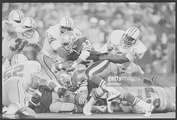 Houston's right defensiveend Jesse Baker grabs a hold of San Francisco's fullback Roger Craig by the waist stopping him from gaining any yardage...