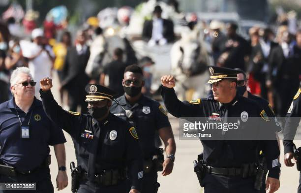 Houston Police Chief Art Acevedo and another officer raise their hands while walking in front of the casket containing the remains of George Floyd,...