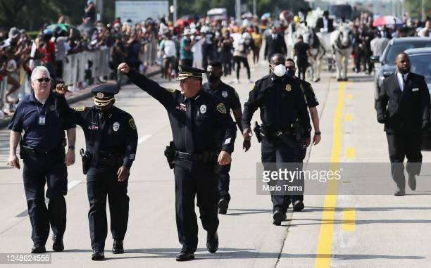 Houston Police Chief Art Acevedo and another police officer raise their hands while walking in front of the casket containing the remains of George...