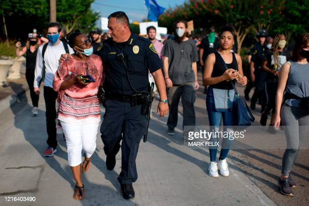 Houston Police Chief Art Acevedo walks arminarm with a woman during a Justice for George Floyd event in Houston Texas on May 30 after George Floyd an...