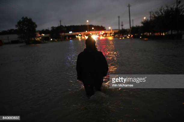 Houston resident walks through waist deep water while evacuating her home after severe flooding following Hurricane Harvey in north Houston August 29...
