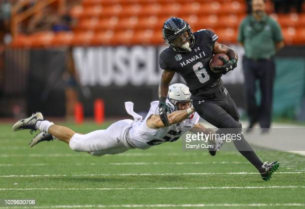 Houston Robert of the Rice Owls makes a diving attempt to tackle Cedric Byrd of the Hawaii Rainbow Warriors during the first quarter of their game at...