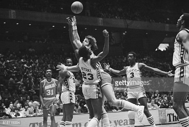 Houston Rocket guard Mike Newlin charges into and shoots over Sixers forward Joe Bryant during a game at the Spectrum Sports Arena in Philadelphia