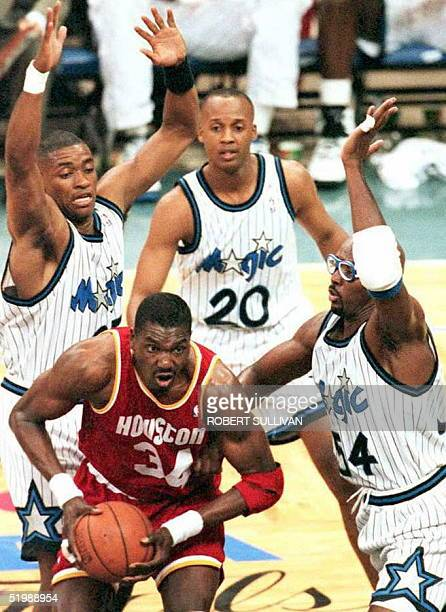 Houston Rockets center Hakeem Olajuwon is triple teamed by Orlando Magic's Nick Anderson Brian Shaw and Horace Grant 07 June during the first quarter...