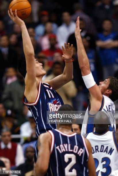 Houston Rockets' center Yao Ming takes a shot over Wasington Wizards' center Christian Laettner and Wizards guard Michael Jordan during fourth...