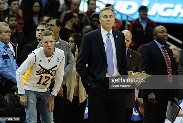 Houston Rockets fan watches a break in the action alongside the bench and Los Angeles Lakers head coach Mike D'Antoni during the game at Toyota...