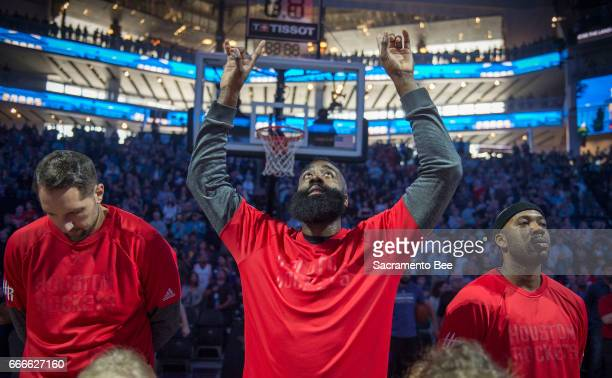 Houston Rockets guard James Harden raises his hands to the air as he's accompanied by teammates forward Ryan Anderson left and forward Ryan Anderson...