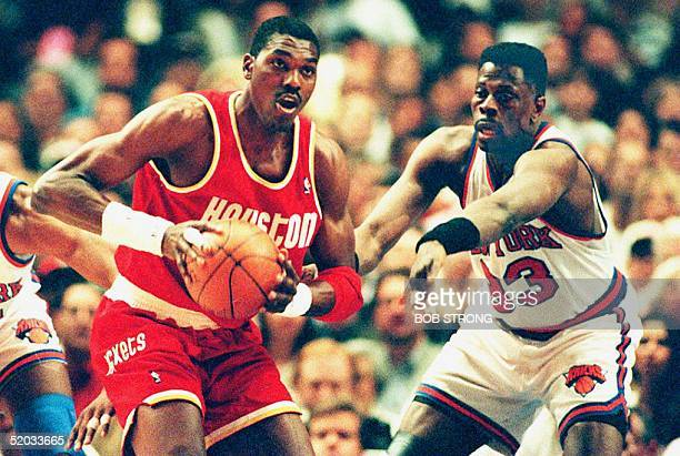 Houston Rockets' Hakeem Olajuwon looks to pass the ball under defensive pressure from the New York Knicks' Patrick Ewing during the first quarter of...