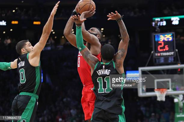 Houston Rockets' James Harden shoots up a desperation threepointer with less than three seconds left on the shot clock as Boston's Jayson Tatum and...