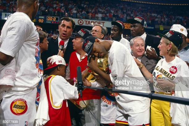 Houston Rockets Owner Leslie Alexander and Head Coach Rudy Tomjanovich speak to the media as Sam Cassell holds the Championship Trophy after winning...