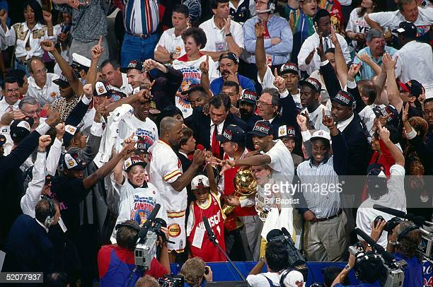 Houston Rockets Owner Leslie Alexander and Head Coach Rudy Tomjanovich speak to the media as Sam Cassell waves to fans behind the championship trophy...