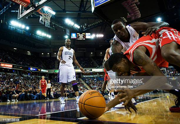 Houston Rockets point guard Aaron Brooks tries to keep the ball in bounds as Sacramento Kings center Samuel Dalembert defends in the second half at...