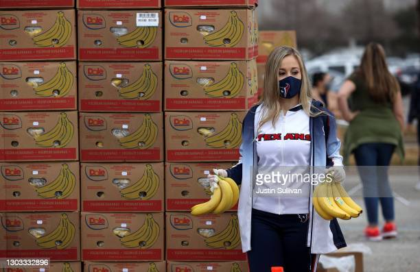 Houston Texans cheerleader holds bananas as she waits to place them in a car during the Houston Food Bank food distribution at NRG Stadium on...
