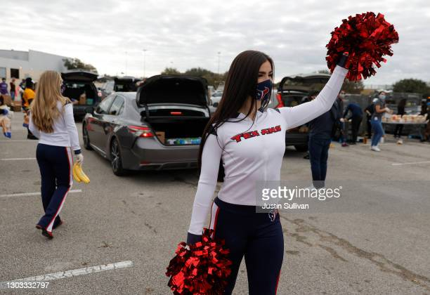 Houston Texans cheerleader uses pom poms to direct traffic during the Houston Food Bank food distribution at NRG Stadium on February 21, 2021 in...