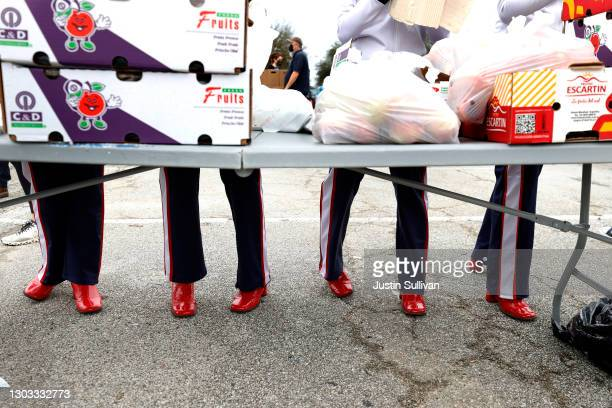 Houston Texans cheerleaders pack bags of peaches during the Houston Food Bank food distribution at NRG Stadium on February 21, 2021 in Houston,...