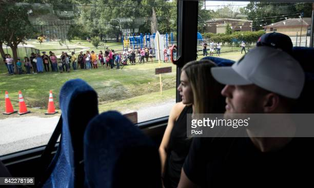 Houston Texans defensive end JJ Watt and his girlfriend Kealia Ohai look out the window at the line of people impacted by Hurricane Harvey waiting...