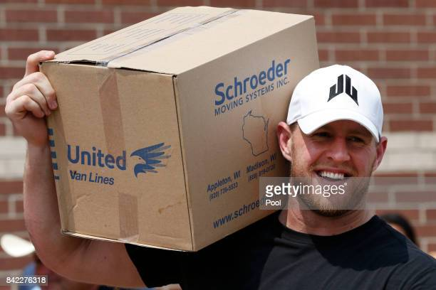 Houston Texans defensive end JJ Watt holds a box of relief supplies on his shoulder while handing them out to people impacted by Hurricane Harvey on...