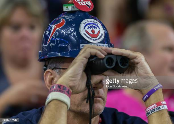 Houston Texans fan uses binoculars to look at the field during the football game between the Kansas City Chiefs and Houston Texans on October 8 2017...