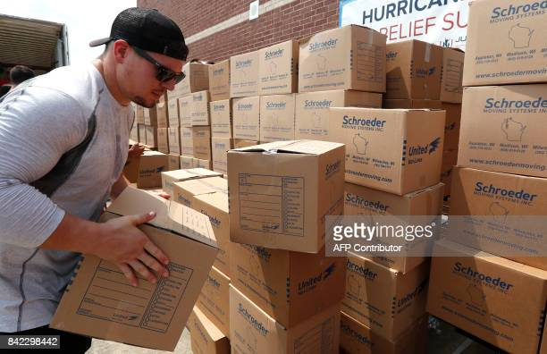 Houston Texans fullback Jay Prosch stacks boxes of relief supplies while distributing them to people impacted by Hurricane Harvey on September 3 in...