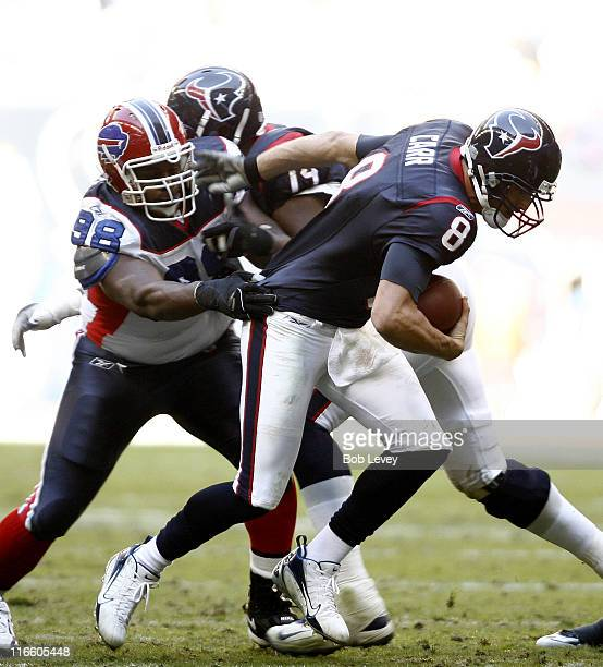 Houston Texans quarterback David Carr eludes the grasp of Buffalo Bills defensive tackle Larry Tripplett as he scrambles out of the pocket during...