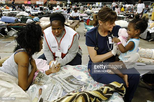 Hurricane Katrina evacuee Kim White speaks with a Red Cross chaplain who did not want to be identified as nurse Sherri Locke from Wichita Kansas...