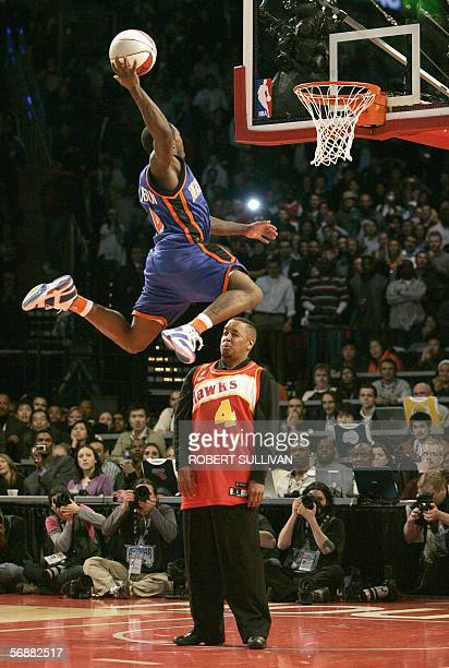 Nate Robinson of the New York Knicks jumps over retired NBA star Spud Webb during the Rising Star Slam Dunk contest 18 February 2006 part of the 2006...