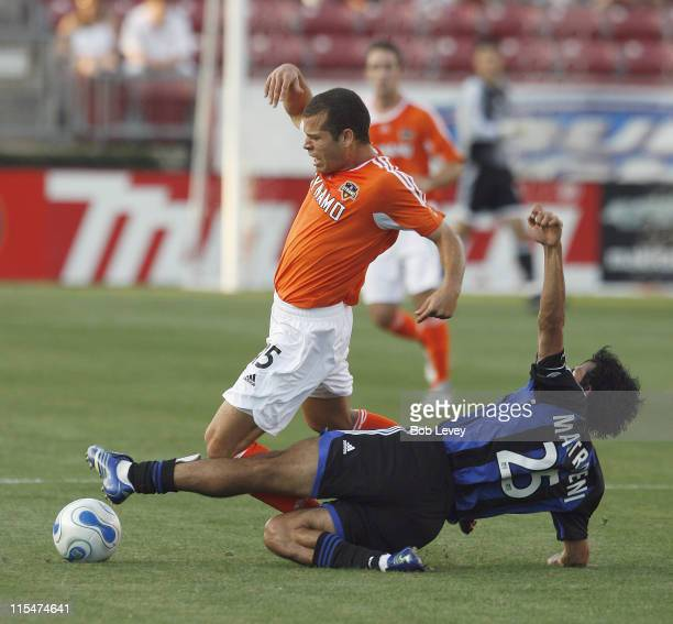 Houston's Alejandro Moreno is brought down hard by Colorado's Pablo Mastroeni during first half action between the Colorado Rapids and the Houston...