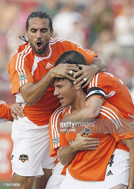 Houston's Brian Ching is congratulated by Dwayne De Rosario and Alejandro Moreno after his first goal during first half action between the Colorado...