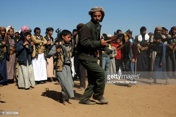 Houthi child fighter and a man carry rifles as they perform the Yemeni traditional Barra dance as part of a tribal gathering staged to reinforce...